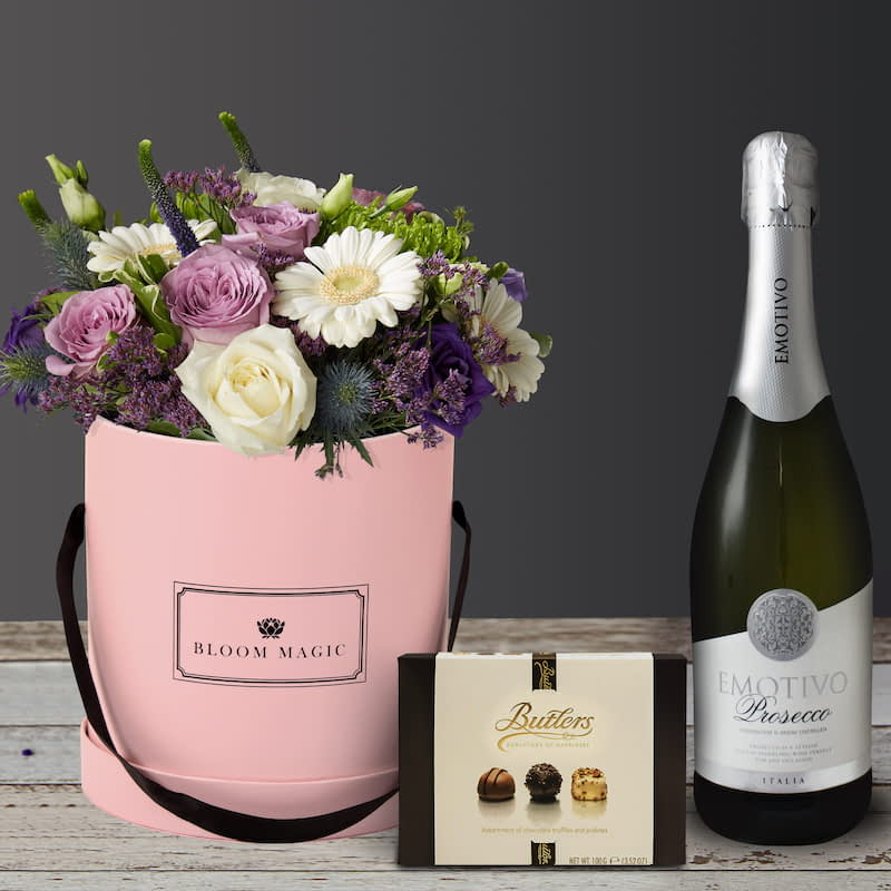 S'aimer Sur Le Pont Neuf Gift Set Flowers Delivered - S'aimer sur le Pont Neuf is a wonderful arrangement of flowers delivered in a blush pink hatbox. The S'aimer sur le Pont Neuf features white avalanche roses, purple lisianthus, and white mini-gerbera. The  S'aimer sur le Pont Neuf would make a perfect arrangement of flowers for the arrival of a new baby boy or as birthday flowers. Whatever the occasion these flowers would be sure to please!
