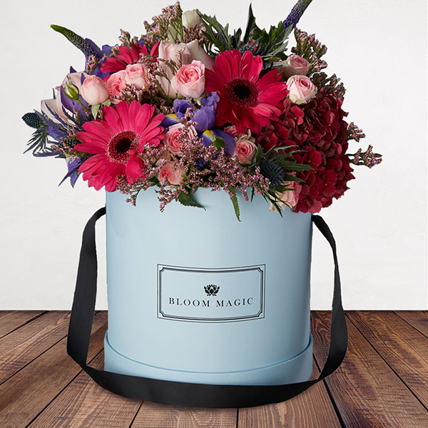 Les Jardins Du Louvre Flowers Delivered - This beautiful hatbox arrangement features hydrangea, pink roses and germini, and rich purple iris, expertly arranged by hand and presented in your choice of a powder blue or charcoal grey hatbox. The warm colours from the flowers gives off a warm winter glow that would heat up any home. 