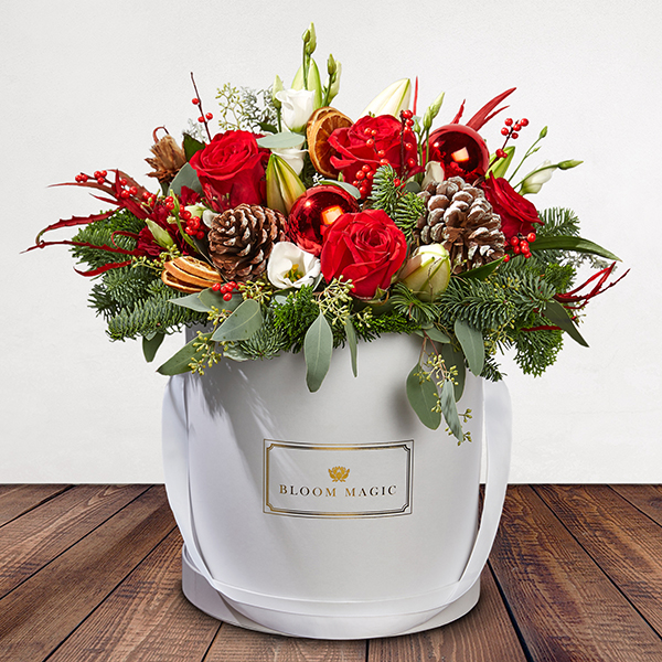 Le Père Noël Flowers Delivered - Our holiday hatbox arrangement is sure to bring festive cheer to any home. Filled with gorgeous seasonal blooms in warm tones set artfully in our gorgeous pearl white hatbox.