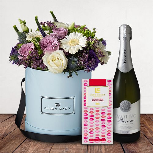 Rêverie à Saint-germain Gift Set Flowers Delivered - This beautiful flower arrangement features a mixture of purple and white roses, lisianthus, and gerbera. It is expertly arranged by hand and presented in your choice of a powder blue or charcoal grey hatbox.