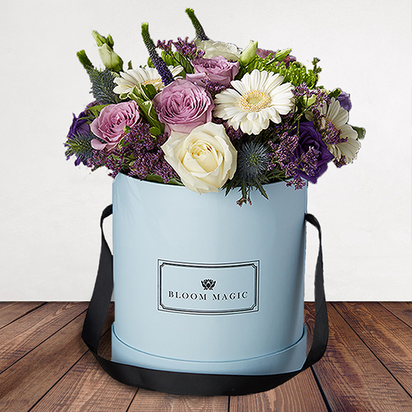 S'aimer sur le Pont Neuf is a wonderful arrangement of flowers delivered in a baby blue hatbox. The S'aimer sur le Pont Neuf features white avalanche roses, purple lisianthus, and white mini-gerbera. The  S'aimer sur le Pont Neuf would make a perfect arrangement of flowers for the arrival of a new baby boy or as birthday flowers. Whatever the occasion these flowers would be sure to please!