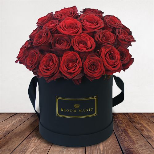 Romance Sur La Seine Flowers Delivered - Our signature Hatbox flower arrangement featuring 24 stunning red roses immaculately arranged and presented in your choice of a matte black or pearl white large hatbox.
