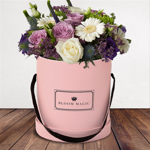S'aimer Sur Le Pont Neuf Flowers Delivered - S'aimer sur le Pont Neuf is a wonderful arrangement of flowers delivered in a blush pink hatbox. The S'aimer sur le Pont Neuf features white avalanche roses, purple lisianthus, and white mini-gerbera. The  S'aimer sur le Pont Neuf would make a perfect arrangement of flowers for the arrival of a new baby boy or as birthday flowers. Whatever the occasion these flowers would be sure to please!