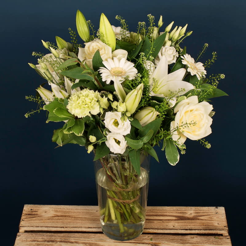 Blooming Whites Flowers Delivered - A classic flower arrangement consisting of white lily's, avalanche roses, and White mini Gerbera that pop when combined with the green carnations. This is a beautiful bouquet that emulates any country garden.  No two bouquets are ever the same. Each Bloom Magic bouquet is bespoke and truly unique. We always use the freshest seasonal blooms available. The photo shows an example of our bouquet with yours containing seasonal flowers similar in colour, texture and vibrancy.