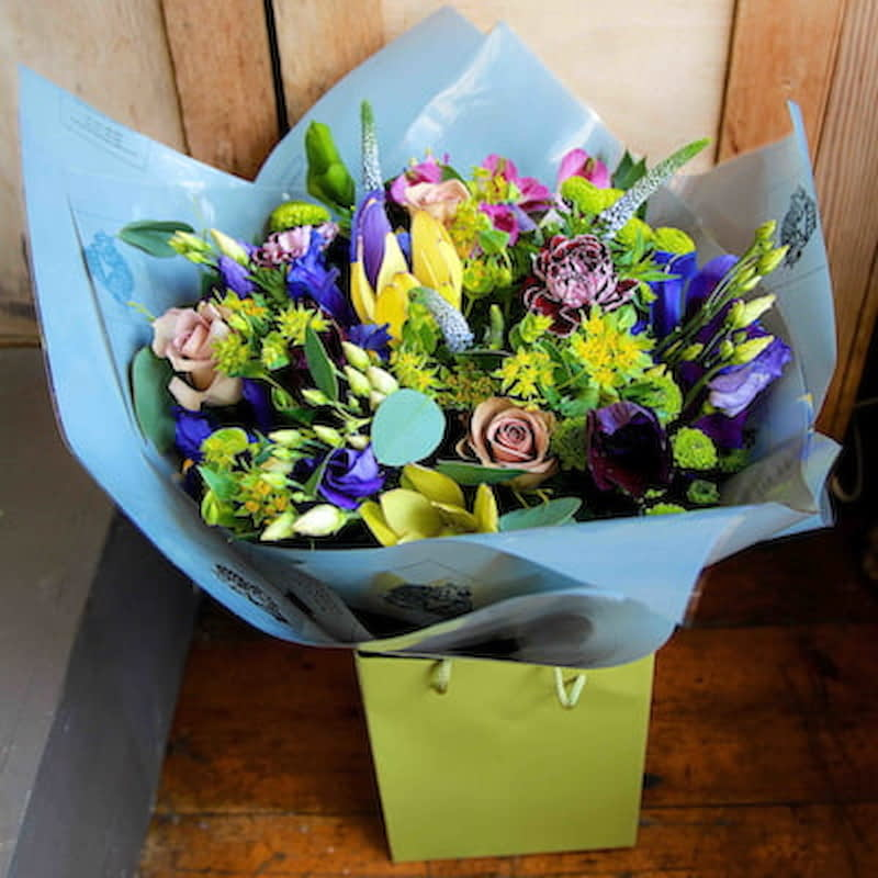 Poseidon Flowers Delivered - A flower arrangement in the shades of the seven seas: bright blues, muted lilacs and deep purple are set off by vivid lime green. These flowers are the perfect gift for any occasion.  No two bouquet are ever the same so each and every bouquet is bespoke and truly unique. The picture shows an example of our bouquet with yours containing seasonal flowers similar in colour, texture and vibrancy.