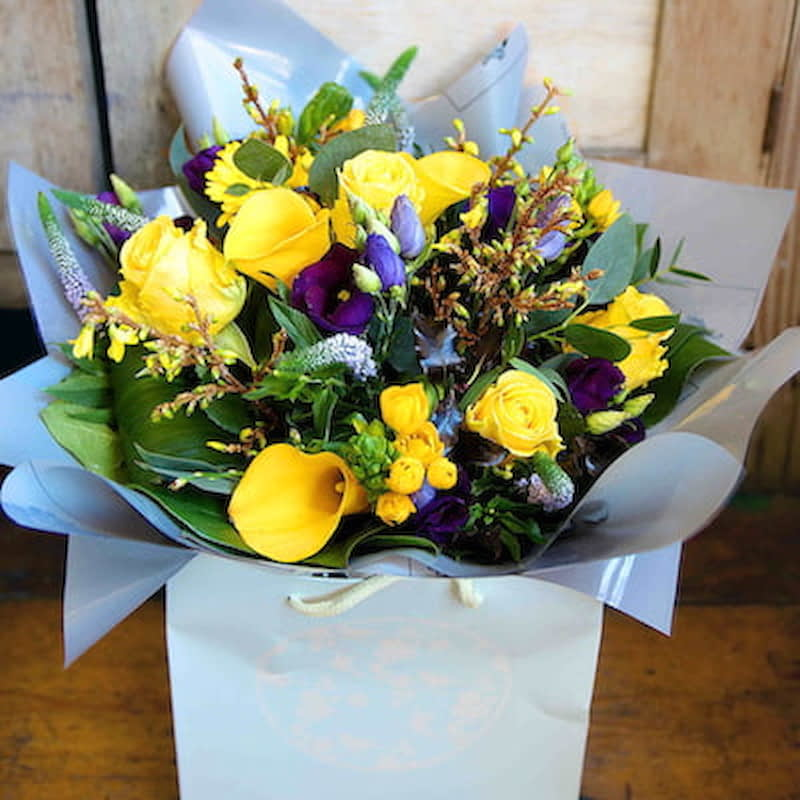 Gaia Flowers Delivered - Sunny yellow and rich purple flowers make this a particularly expressive Summer flower arrangement. Lively and happy, 'Gaia' is sure to deliver a flowery smile.