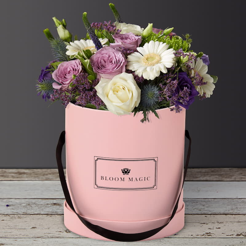 S'aimer Sur Le Pont Neuf Flowers Delivered - S'aimer sur le Pont Neuf is a beautiful arrangement of hatbox flowers features a mixture of purple and white roses, lisianthus, and gerbera. This hatbox is expertly arranged by hand and presented in your choice of a blush pink, powder blue or charcoal grey hatbox. The S'aimer sur le Pont Neuf is perfect for any occasion and we guarantee it will put a big smile on her face!