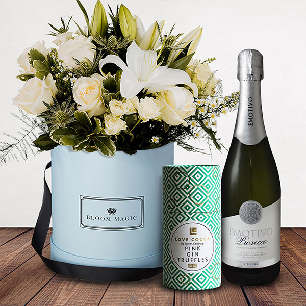 La Neige à Paris Gift Set Flowers Delivered - This mix of whites featuring rose, lilies and variegated pittos creates the breathtaking 'La neige à Paris.' A classic and luxurious hatbox, makes this suitable for any occasion. The giftset comes complete with a bottle of prosecco as well as luxury Love Cocoa pink gin truffles.
