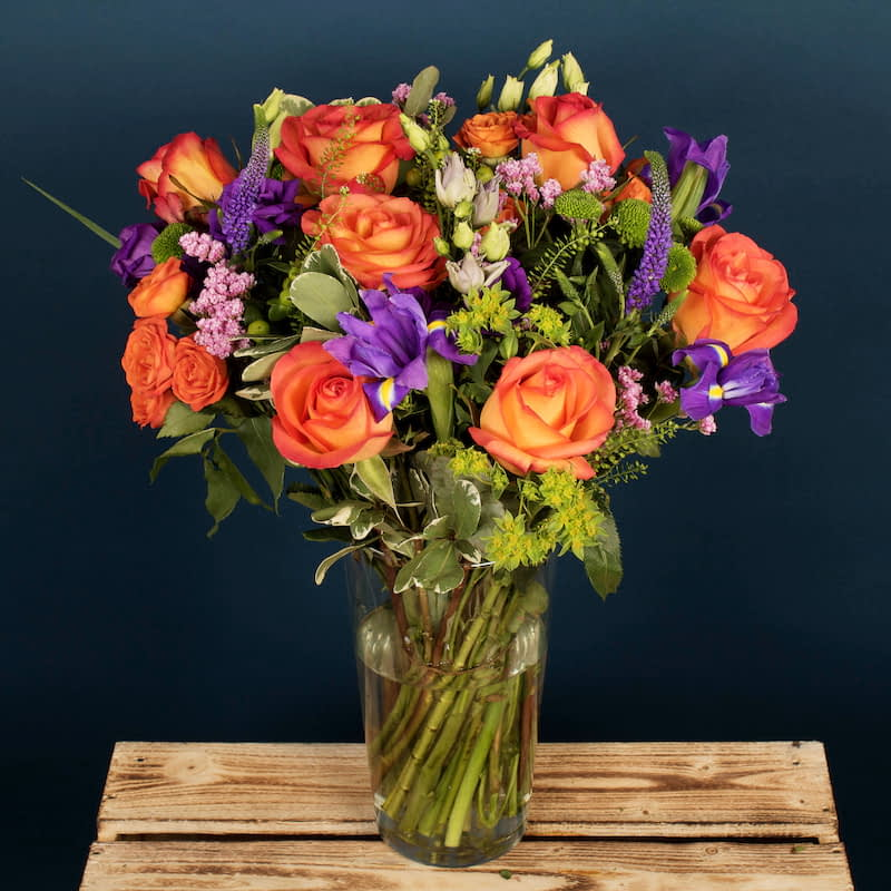 Summer Sunset Flowers Delivered - The wonderful Summer Sunset bouquet features full-headed orange blush roses, whose tones are reminiscent of a sunset over the red rocks of Arizona. The Purple iris and lisianthus compliment the orange roses and make this bouquet mesmerizing. This warm and vibrant bouquet is perfect for any occasion, whether friendly or romantic.