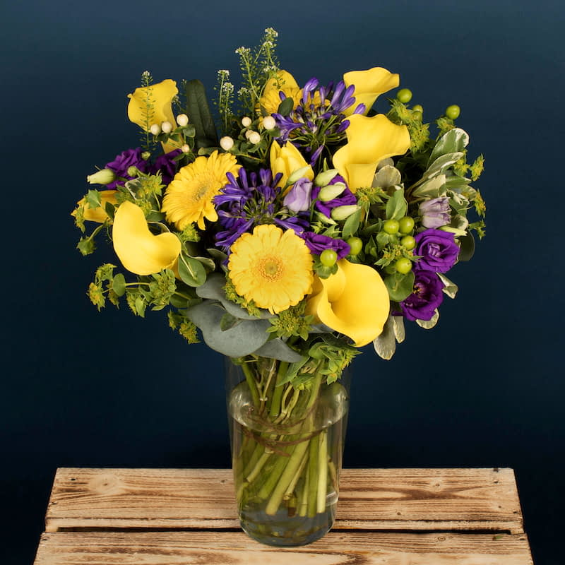 "Spring Meadow Flowers Delivered - Nothing says ""Spring"" like bright yellow tulips and lilies. Shoots of hypericum and agapanthus give this bouquet the feeling of a wild mountain meadow. This wonderful and uplifting bouquet was crafted to guarantee smiles and positive energy.  This bouquet would be perfect as a Congratulations gift, for a Birthday or as a Get Well Soon gesture. 
