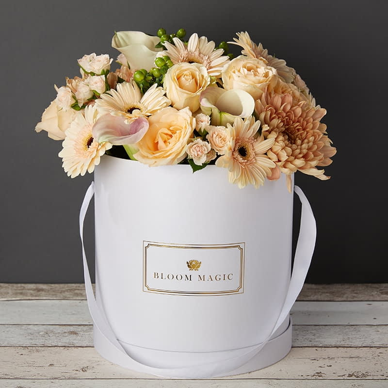 Bloom Magic - Flower Delivery Ireland - This bouquet screams white, and would brighten up any home or day. This arrangement comes in a pearl white, or matte black hatbox. It features white calla lilies, and white roses, that are hand tied by some of the c