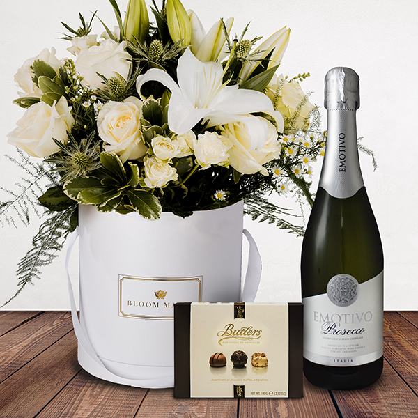 La Neige à Paris Gift Set Flowers Delivered - This mix of whites featuring rose, lilies and variegated pittos creates the breathtaking 'La neige à Paris.' A classic and luxurious hatbox, makes this suitable for any occasion. The giftset comes complete with a bottle of prosecco as well as luxury chocolates.