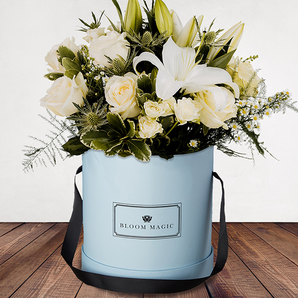 La Neige à Paris Flowers Delivered - This mix of whites featuring rose, lilies and variegated pittos creates the breathtaking 'La neige à Paris.' A classic and luxurious hatbox, makes this suitable for any occasion.