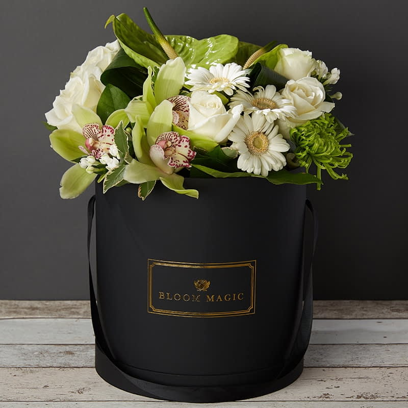Le Jardin De Monet Flowers Delivered - Available in your choice of a matte black or pearl white hatbox, this chic and contemporary arrangement contains a beautiful mix of white roses and gerbera, along with green orchids, anthuriums, and bouvardia. This hatbox bouquet is extremetly suitable for the modern home. 