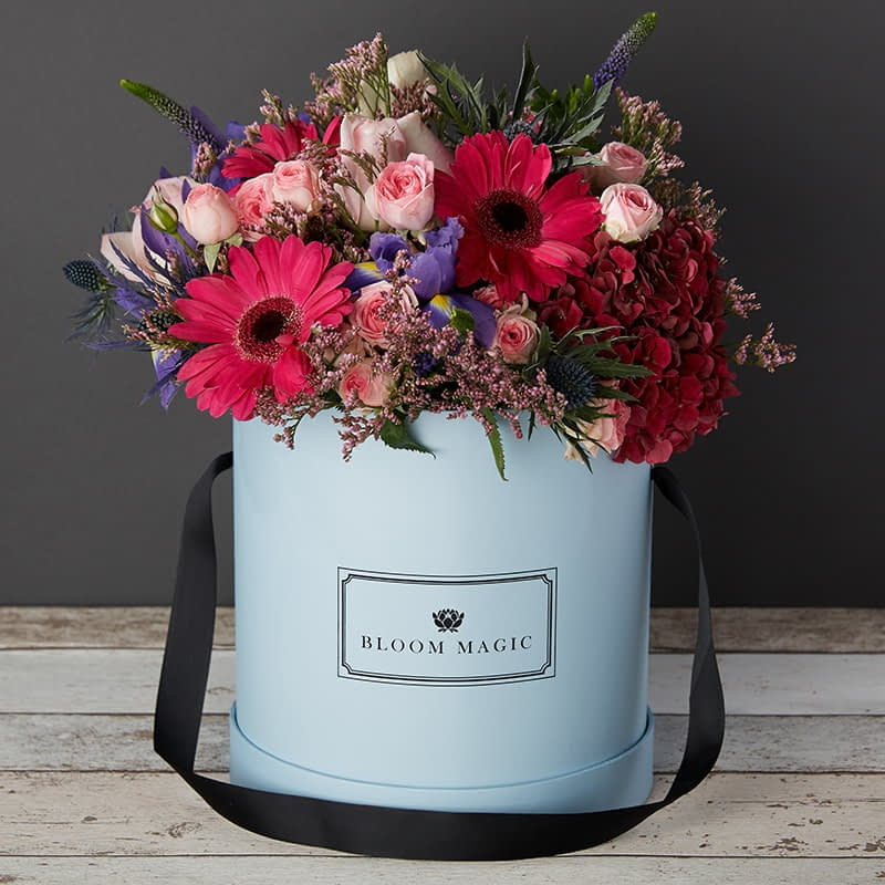 Bloom Magic - Flower Delivery Ireland - A warm bouquet containing pink roses, red hydrangea, pink roses, and rich purple iris. This flower arrangement comes hand tied in one of our beautiful hatboxes. The luxurious flowers are available for delivery to an