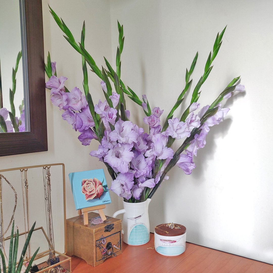 """New! Bloom Magic are delighted to offer this limited edition hand tied bouquet of a dozen fresh purple gladiolus. This expressive bouquet blooms from the bottom up creating """"tall spikes"""".  A unique gift making for an impressive display in any room.  Colour may vary. Please note : No two bouquet are ever the same so each and every bouquet is bespoke and truly unique. The picture shows an example of our bouquet with yours containing seasonal flowers similar in colour, texture and vibrancy.   Note: On delivery, you may notice some tougher, slightly browned petals around the outside of your roses or other flowers. Rest assured, the flowers are fresh!These are called 'storm petals' which we intentionally leave on to protect the delicate inner flower when in transit. To reveal the fresh inner petals, gently remove the 3/4 storm petals by pulling them at the base"""