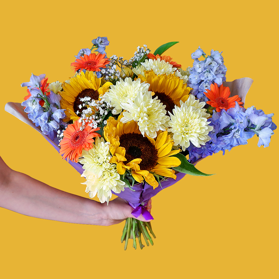 """Sunflower Sky Flowers Delivered - Brand new to the Californian collection, 'sunflower sky' is a dreamy bouquet made up of yellow spray rose, blue delphinium, sunflowers & more.   Sunflowers are known for being """"happy"""" flowers, making them the perfect gift to bring joy to someone's day.  This bouquet is a Bloom Magic limited edition arrangement, order now while stocks last!   One size only.   No two bouquet are ever the same so each and every bouquet is bespoke and truly unique. The picture shows an example of our bouquet with yours containing seasonal flowers similar in colour, texture and vibrancy.  Note: On delivery, you may notice some tougher, slightly browned petals around the outside of your roses or other flowers. Rest assured, the flowers are fresh!These are called 'storm petals' which we intentionally leave on to protect the delicate inner flower when in transit. To reveal the fresh inner petals, gently remove the 3/4 storm petals by pulling them at the base"""