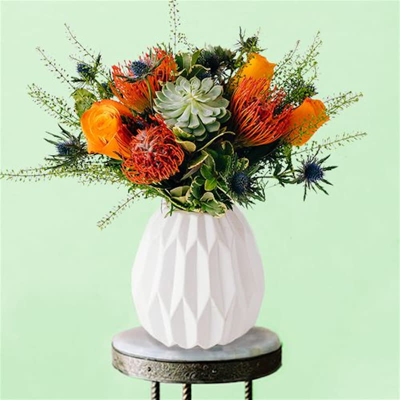 The Knightsbridge Flowers Delivered - Inspired by London and its suburbs, The Knightsbridge bouquet is a dynamic mix of greens, blues & oranges that draws us closer to nature. Vibrant in colour, this bouquet is ideal for celebrations of any kind, from birthdays to anniversaries as it is absolutely bursting with personality and charm.